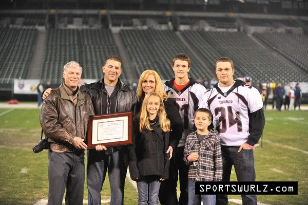 Coach Feliciano and family with his award at the Oakland Coliseum, 12/10/11